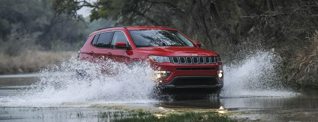 Red 2020 Jeep Compass driving through water