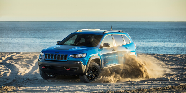 Blue 2020 Jeep Cherokee driving in sand