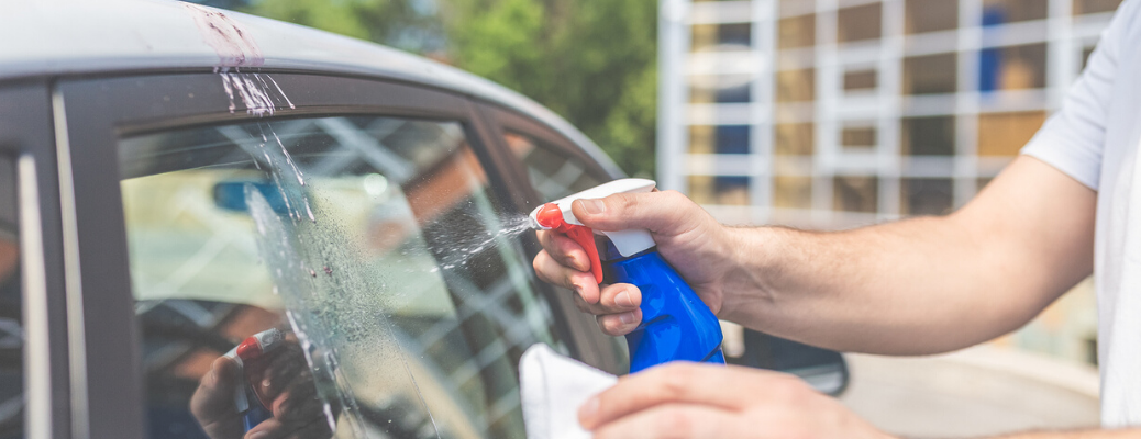 Person using spray bottle to clean bird poop from car