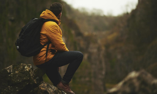 Individual sitting on rock and wearing backpack