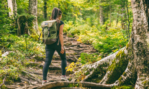 Woman wearing backpack and walking on trail