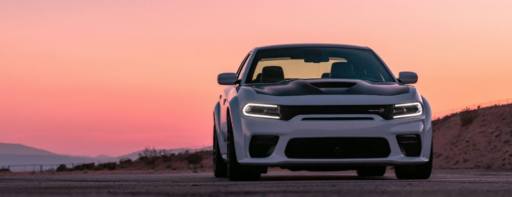 Front view of white 2021 Dodge Charger in front of sunset