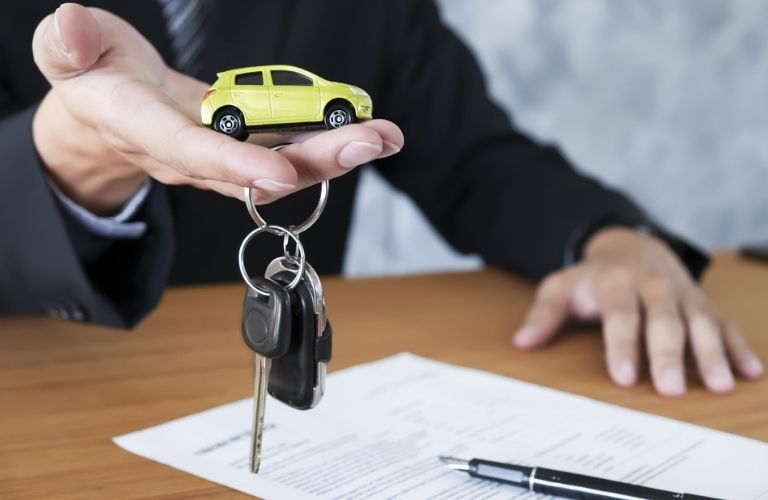 Car keys in hand and loan agreement on top of a table