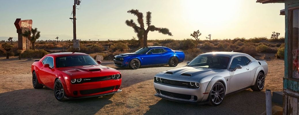 Three 2021 Dodge Challengers parked in a desert area