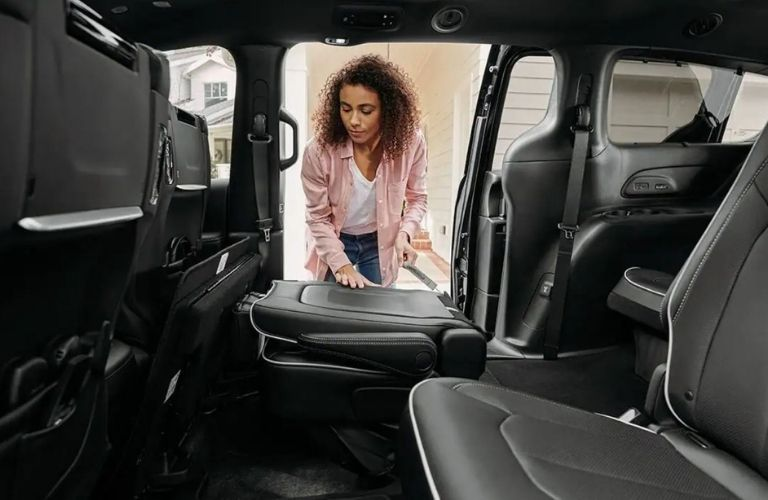 2021 Chrysler Pacifica 2nd Row seats being folded by a woman