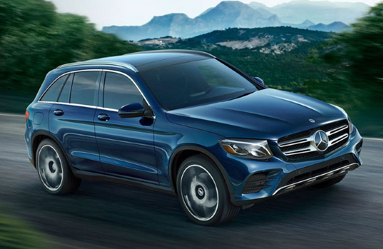 Blue 2020 Mercedes-Benz drives along a highway with a beautiful mountain in the distance.