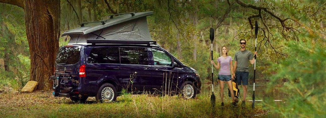 Mercedes-Benz Metris Weekender parked out in a forest with two humans holding paddles.