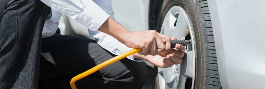 man filling up vehicle tire with air