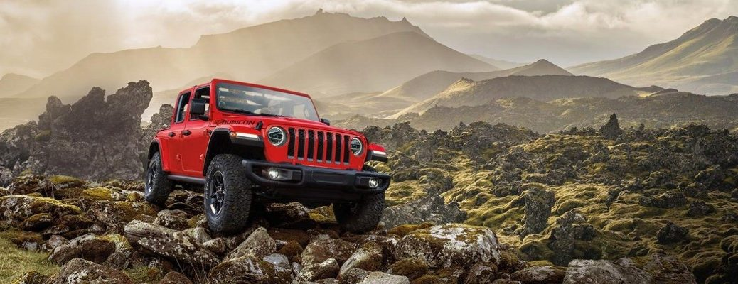2020 Jeep Wrangler exterior shot with red paint parked on rocks with mountain background