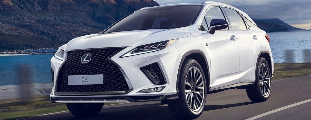 Front view of white 2020 Lexus RX driving on waterfront road