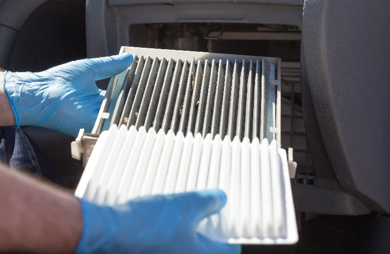 Person changing out an air filter in a vehicle