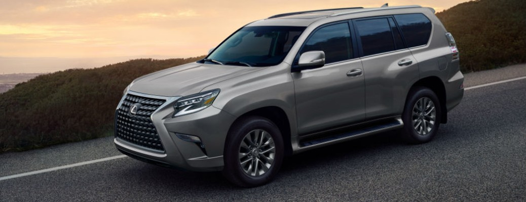 The 2021 Lexus GX driving on a road with the sun setting