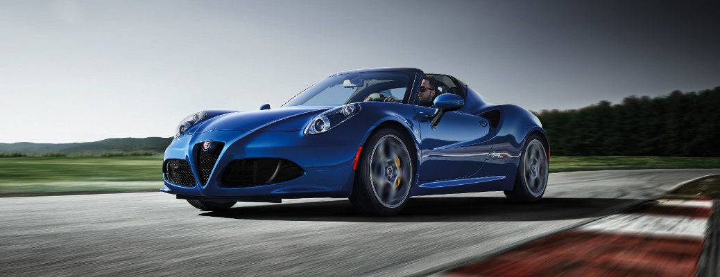 2020 Alfa Romeo 4C Spider exterior shot with blue paint color driving around a race track under a darkening sky