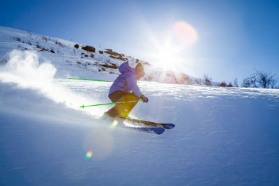 adult skiier coming down snow covered hill sun shining bright