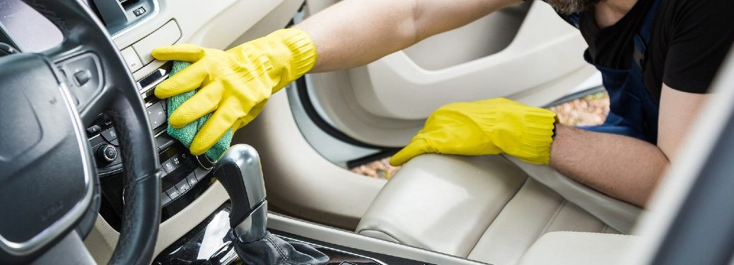 Person wearing gloves and cleaning the interior of a car