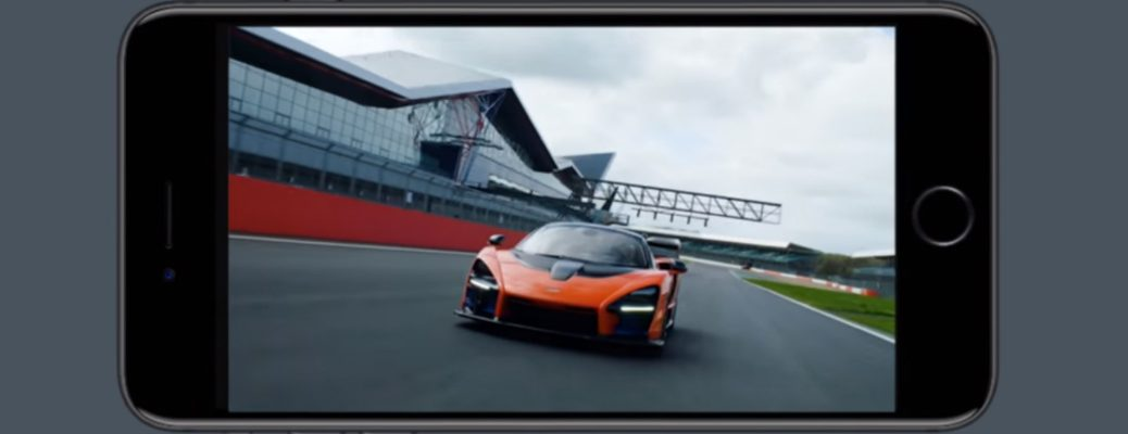 Smartphone showing a video of an orange McLaren vehicle on a race track
