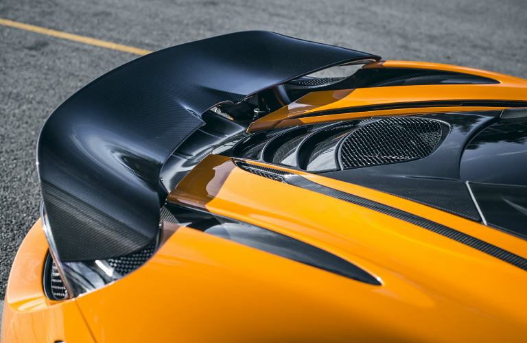 Close-up view of MSO Defined Carbon Fiber Rear Active Spoiler on orange McLaren 720S