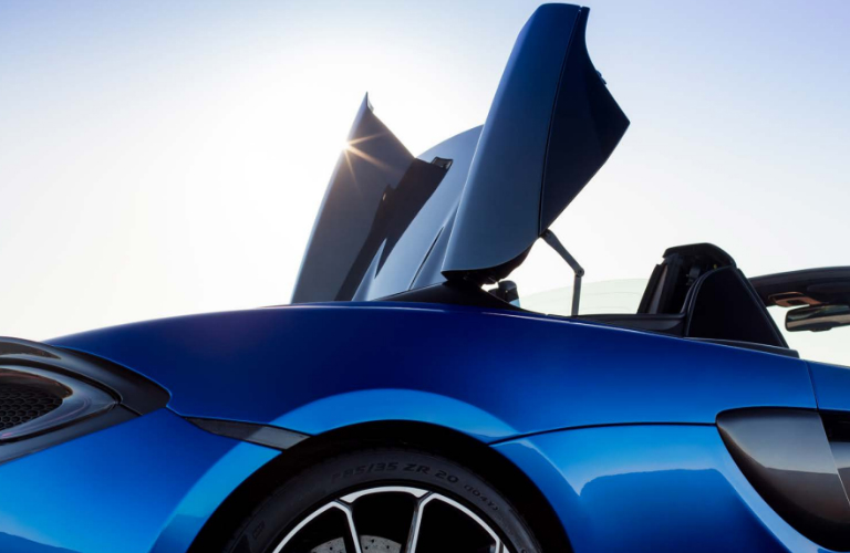Hardtop of blue 2019 McLaren 570S Spider retracting into the tonneau deck