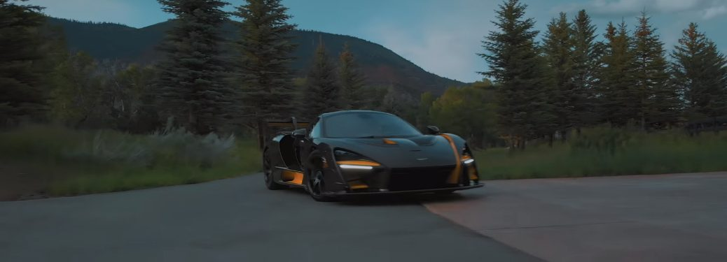 Black and yellow McLaren Senna with mountains in the background
