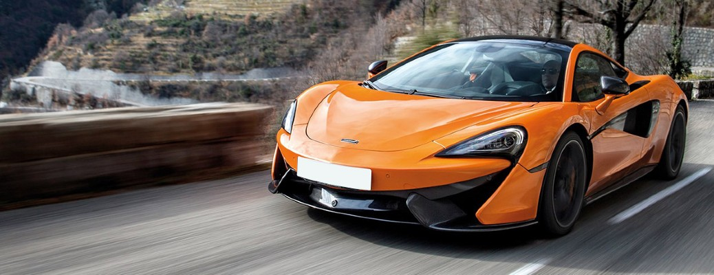 2020 McLaren 570S Coupe orange exterior front fascia driving on bridge
