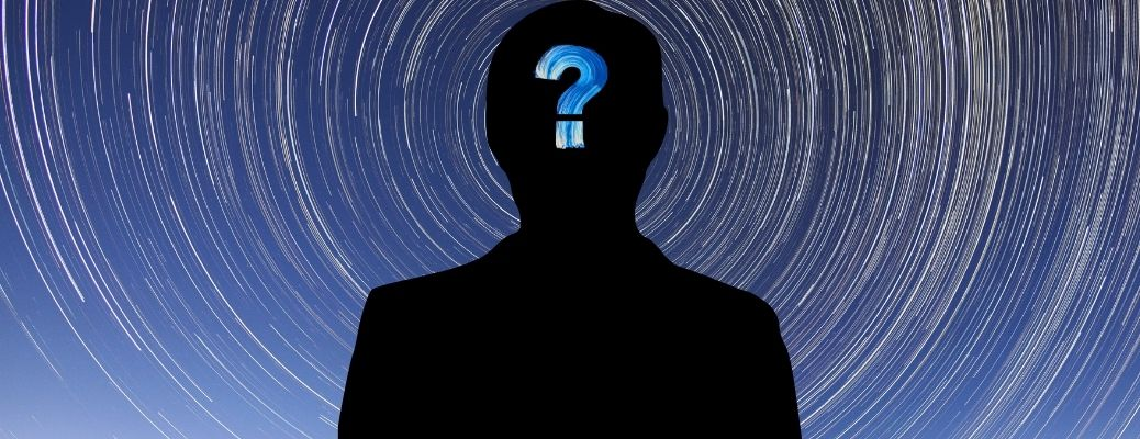 Silhouette of mysterious individual emanating from cosmos with question mark on head