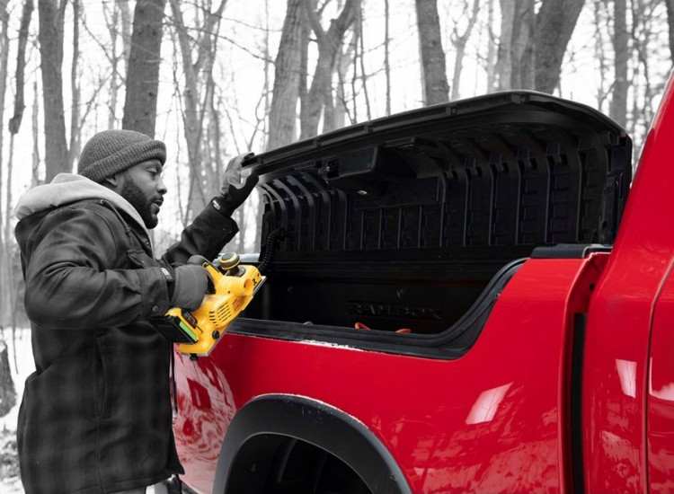 Man putting a tool inside the RamBox storage system on the 2019 Ram 1500