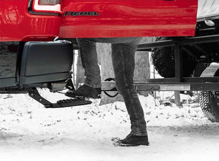 Low angle of a person using the Kick Out Bed Step on the 2019 Ram 1500