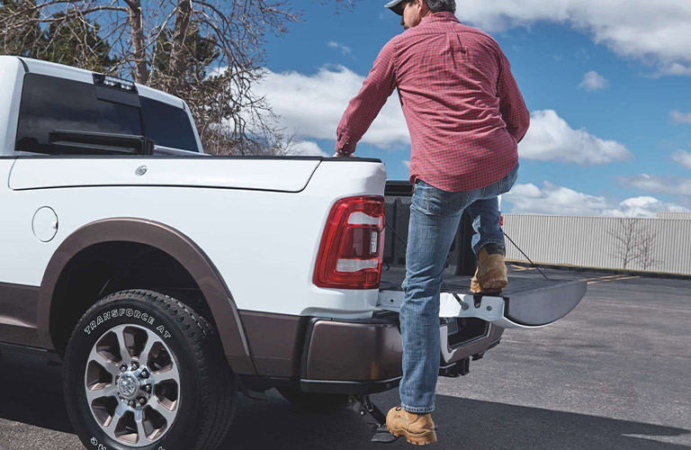 Man climbing into the bed of a 2020 RAM 2500 truck