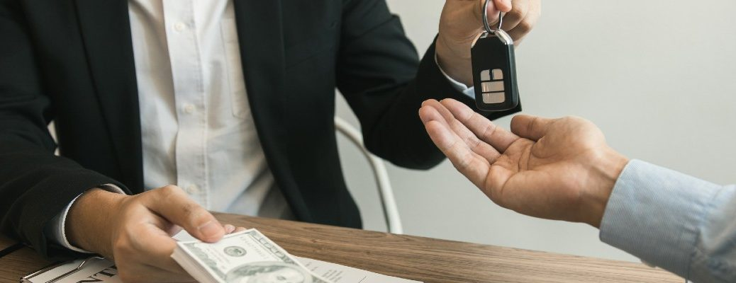 A stock photo of people exchanging money for a set of keys.