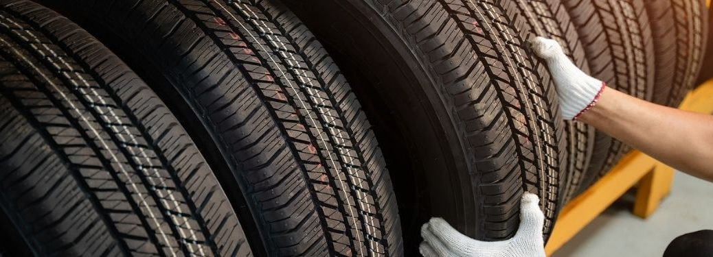 A male hand with gloves pulling out a new tire from a tire rack