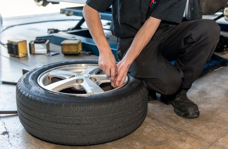 A mechanic kneeling down adjusts tire pressure on a tire kept on the floor