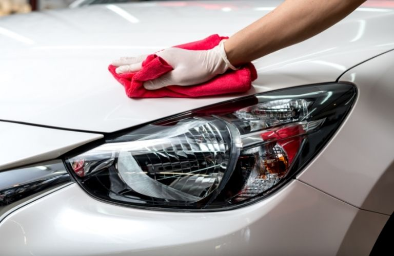 Image of a person wiping the exterior surface of a car