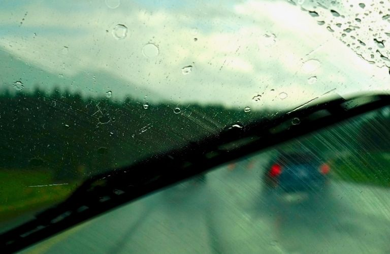 Image of a windshield wiper wiping off small droplets of rain