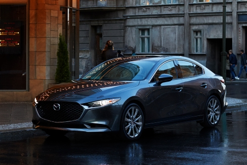 A shiny 2020 Mazda3 is parked by a sidewalk in a wet city.