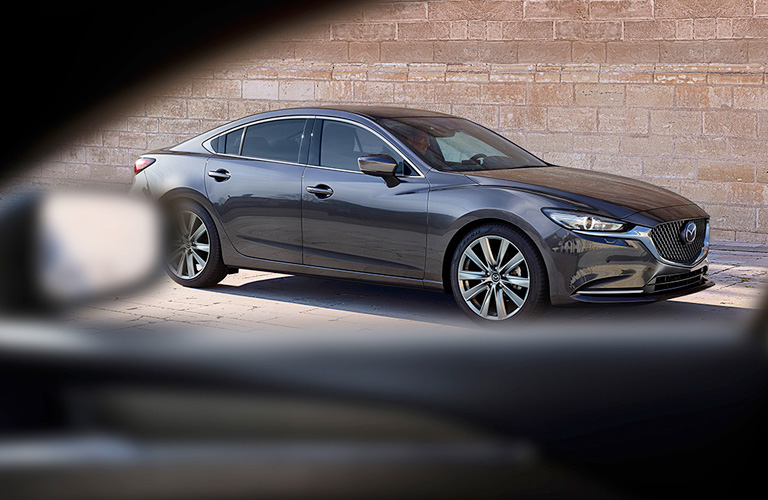 Silver 2020 Mazda6, viewed through a car window and parked by a brick wall.