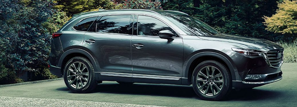 2020 Mazda CX 9 passenger side parked in driveway surrounded by trees