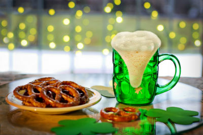 plate of pretzel and green cup of beer