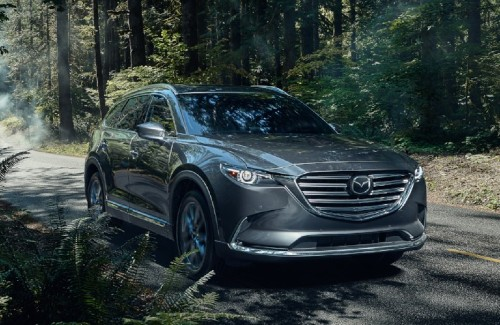 2020 Mazda CX-9 silver exterior front passenger side driving on forest road