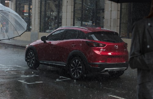 2020 Mazda CX-3 red exterior driver side rear on street in rain people walking with raincoats and umbrellas