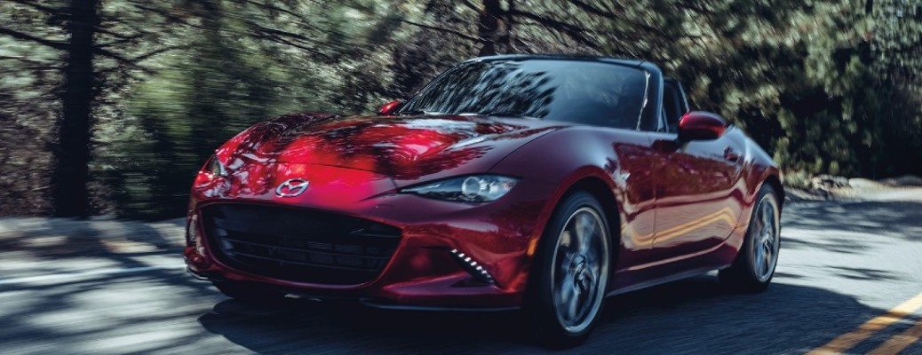 2020 Mazda MX-5 Miata red exterior front driver side driving on forest road daytime