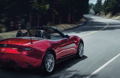 2020 Mazda MX-5 Miata red exterior top down rear passenger side driving on curvy road