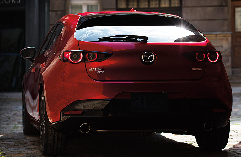 2020 Mazda3 hatchback red exterior rear driver side parked on brick street