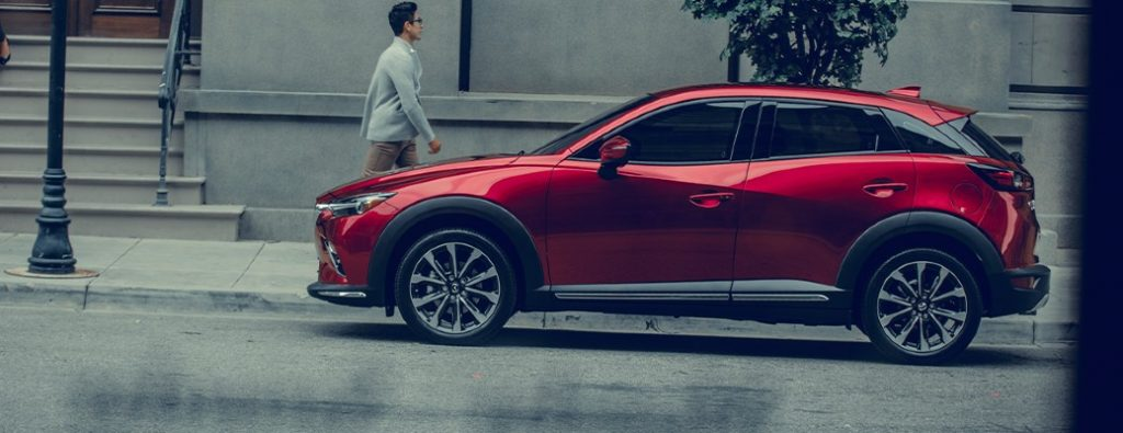 2020 Mazda CX-3 red exterior driver side parked on side of street man walking past