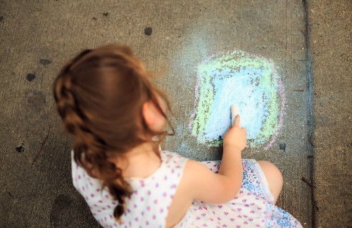 young girl drawing on pavement with sidewalk chalk