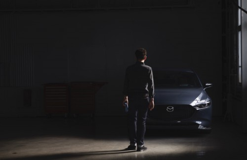 2021 Mazda3 2.5 Turbo grey exterior front parked in garage with window man with back facing camera