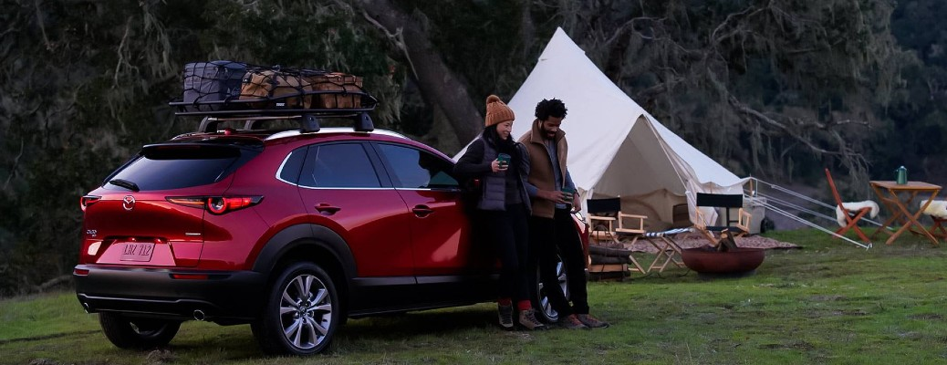 2021 Mazda CX-30 red exterior rear fascia passenger side parked in wilderness couple camping leaning on side drinking coffee
