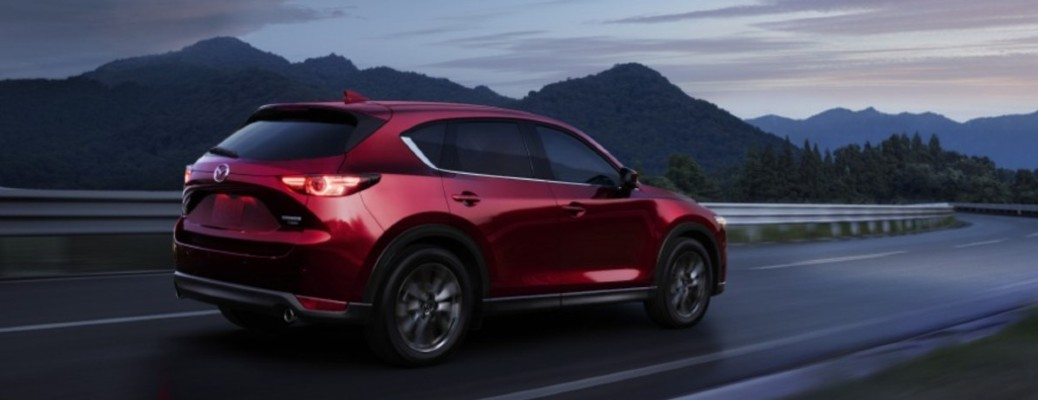 2021 Mazda CX-5 red exterior rear fascia driving on curvy road mountains in background