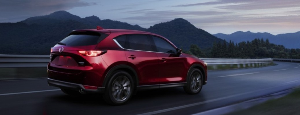 2021 Mazda CX-5 red exterior passenger side rear fascia driving on curved road mountain background