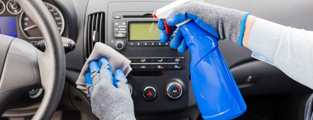 person with gloves on using spray and microfiber towel to clean interior dash of car