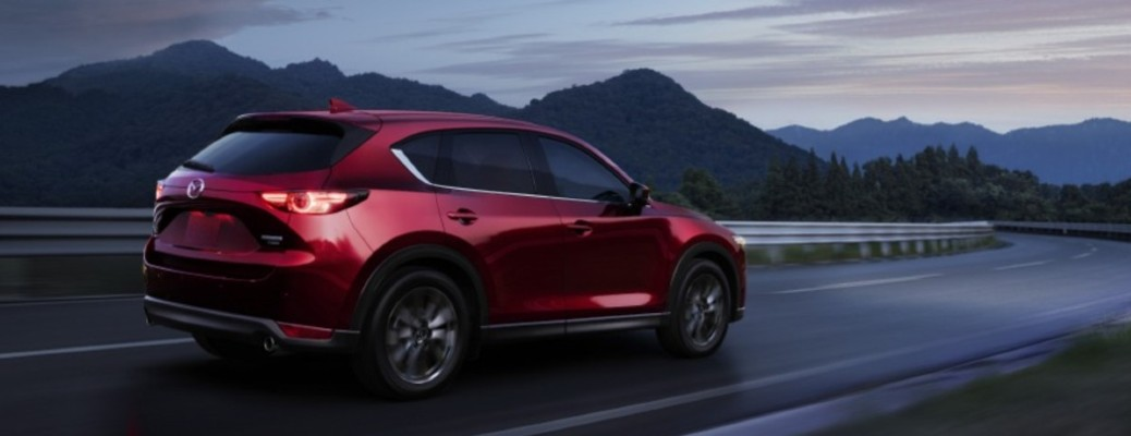 2021 Mazda CX-5 red exterior driving on curvy highway in mountains